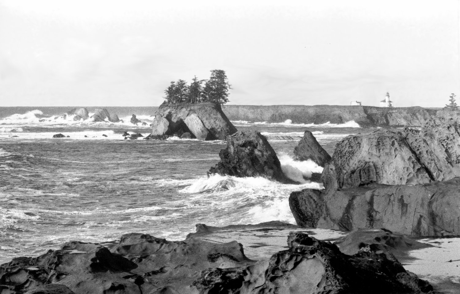 Black and white photo of a rocky beach and surf with a lighthouse in the distance
